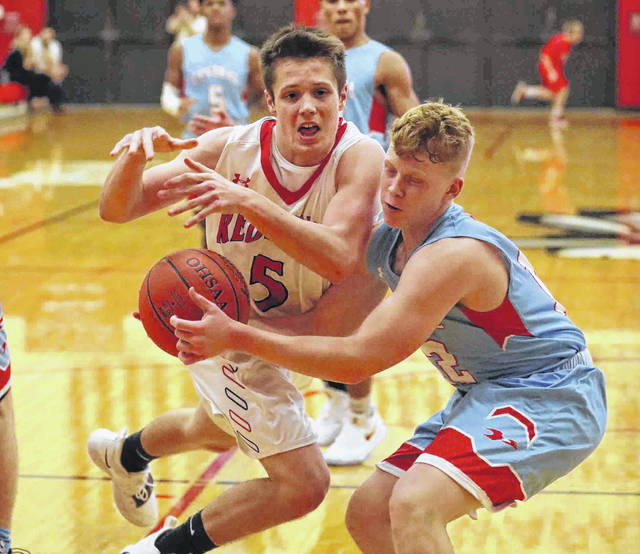 Lima Central Catholic's Nate Stolly ties up Wapakoneta's Noah Ambos (5) as Ambos drives to the basket during Thursday night's game at Wapakoneta.