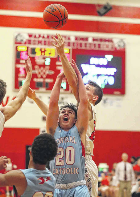 Wapakoneta's Adam Scott looks to outreach Lima Central Catholic's Dominic Riepenhoff for the ball during Thursday night's game at Wapakoneta.
