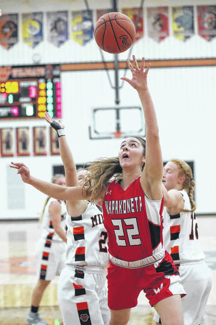 Wapakoneta's Katie Engel puts up a shot against Minster's Courtney Ernst, left, and Danielle Barhorst during Tuesday night's game at Minster. The host Wildcats won the game 54-31. No other game information was reported by deadline.