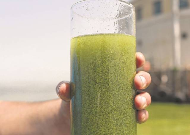 FILE- In this Aug. 3, 2014 photo, a sample glass of Lake Erie water is photographed near the City of Toledo water intake crib, in Lake Erie, about 2.5 miles off the shore of Curtice, Ohio. Ohio and Michigan have agreed to sharply reduce phosphorus runoff blamed for a rash of harmful algae blooms on Lake Erie that have contaminated drinking water supplies and contributed to oxygen-deprived dead zones where fish can't survive, Friday, June 12, 2015. (AP Photo/Haraz N. Ghanbari, File)