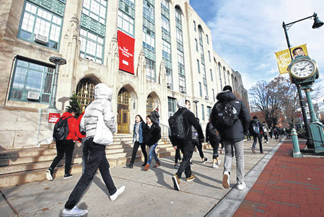 Students and passers-by walk past an entrance to Boston University College of Arts and Sciences in Boston last month. It's OK to borrow some money for school, but the cost of a college education becomes very real if student loan payments affect where you live and work, and how much you can save for the future.