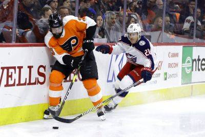 The Flyers' Radko Gudas, left, and Columbus' Riley Nash vie for the puck during Thursday night's game in Philadelphia. Columbus won 4-3 in overtime. (AP photo)