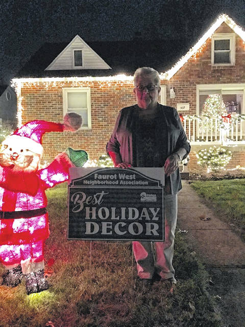 Sally Clemans stands outside her home on Pears Avenue, which won Faurot West Neighborhood Association's Best Holiday Decor contest.