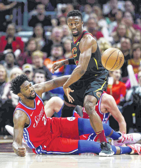 Cleveland Cavaliers' David Nwaba (12) and Philadelphia 76ers' Joel Embiid (21), from Cameroon, battle for the ball during the first half of an NBA basketball game Sunday, Dec. 16, 2018, in Cleveland. (AP Photo/Ron Schwane)