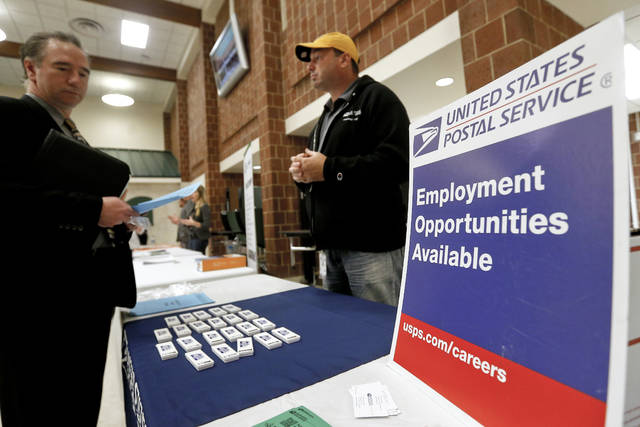 FILE- In this Nov. 2, 2017, file photo a recruiter from the postal service, right, speaks with an attendee of a job fair in the cafeteria of Deer Lakes High School in Cheswick, Pa. Even with fear of a global economic slump depressing stock markets, the jobs report for December is expected to offer reassurance that the U.S. economy remains sturdy and on track to expand for a 10th straight year.