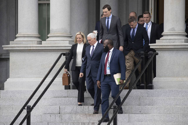 Homeland Security Secretary Kirstjen Nielsen, left, Vice President Mike Pence, White House legislative affairs aide Ja'Ron Smith, followed by White House Senior Adviser Jared Kushner, and others, walk down the steps of the Eisenhower Executive Office building, on the White House complex, after a meeting with staff members of House and Senate leadership, Saturday, Jan. 5, 2019, in Washington. (AP Photo/Alex Brandon)