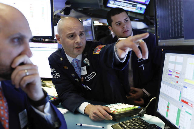 FILE- In this Jan. 4, 2019, file photo Mario Picone, center, works with fellow specialists on the floor of the New York Stock Exchange. The U.S. stock market opens at 9:30 a.m. EST on Monday, Jan. 7. (AP Photo/Richard Drew, File)