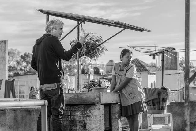 "This image released by Netflix shows filmmaker Alfonso Cuaron, left, and actress Yalitza Aparicio on the set of ""Roma."" Cuaron, Bradley Cooper and Spike Lee are among the nominees for the Director's Guild award for outstanding directorial achievement. The DGA announced its five nominees Tuesday in one of the most closely watched guild awards leading up next month's Academy Awards.  (Carlos Somonte/Netflix via AP)"
