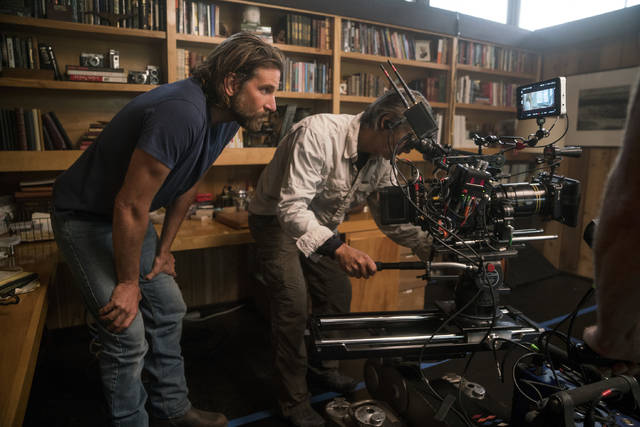 "This image released by Warner Bros. Pictures shows director/co-writer/producer Bradley Cooper, left, and camera operator Scott Sakamoto on the set of ""A Star is Born."" Cooper, Alfonso Cuaron and Spike Lee are among the nominees for the Director's Guild award for outstanding directorial achievement. The DGA announced its five nominees Tuesday in one of the most closely watched guild awards leading up next month's Academy Awards.  (Clay Enos/Warner Bros. via AP)"