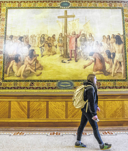 Kristin Fabian walks by a mural of Christopher Columbus at Notre Dame in South Bend, Ind., in November 2017. The University of Notre Dame will cover murals in a campus building that depict Christopher Columbus in America, the school's president said, following criticism that the images depict Native Americans in stereotypical submissive poses before white European explorers.
