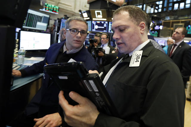 FILE- In this Jan. 18, 2019, file photo specialist Anthony Rinaldi, left, and trader Robert Gasparino work on the floor of the New York Stock Exchange. The U.S. stock market opens at 9:30 a.m. EST on Tuesday, Jan. 22.  (AP Photo/Richard Drew, File)
