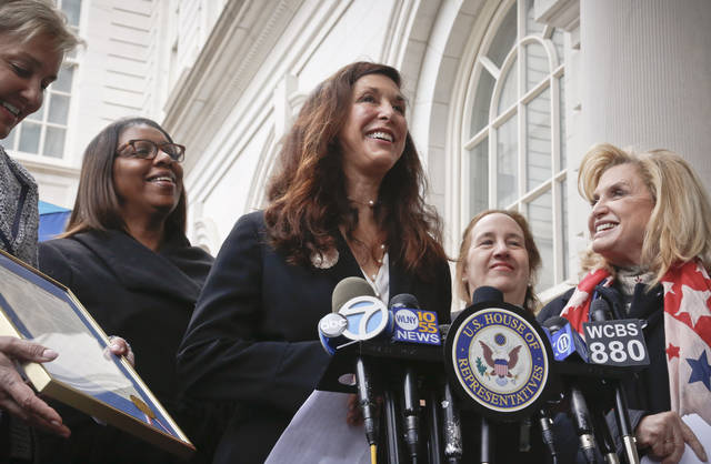 """FILE - In this March 27, 2017 file photo """"Fearless Girl"""" statue creator Kristen Visbal, center, speaks after being recognized by U.S. Rep. Carolyn B. Maloney, far right, during a news conference at City Hall in New York.  Visbal is being sued by a group that says she failed to make a 9-foot (2.7-meter) bronze replica of Alexander Hamilton.  U.S. Coast Guard Academy Alumni Association's lawsuit says Kristen Visbal breached a $28,000 contract to create the statue.  (AP Photo/Bebeto Matthews, File)"""