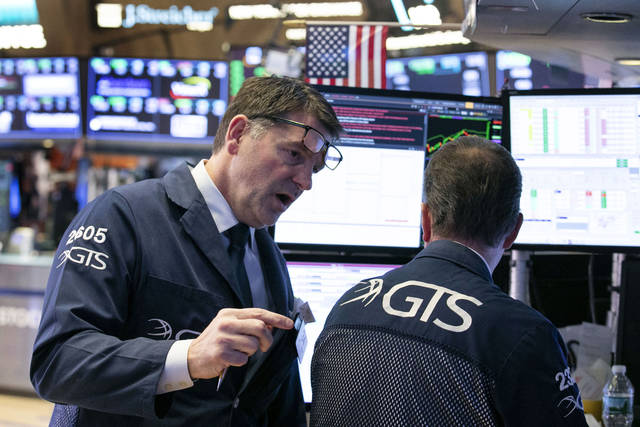 Specialist David Haubner, left, talks with a colleague as they work on the floor of the New York Stock Exchange, Wednesday, Jan. 30, 2019. Fed officials ended a two-day meeting on Wednesday by keeping the federal funds rate — what banks charge each other — at a range of 2.25 to 2.50 percent. (AP Photo/Richard Drew)