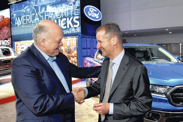 Jim Hackett, president and chief executive officer, Ford Motor Company, and Herbert Diess, chief executive officer, Volkswagen Group, tour the Ford display Monday at the 2019 North American International Auto Show.
