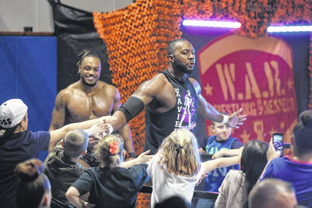 Xavier Walker gives a high five to fans as he enters a match during the Wrestling and Respect New Year's Knockout held Jan. 5 at the Bradfield Community Center. W.A.R. Ohio has been staging shows in Lima for 16 years.