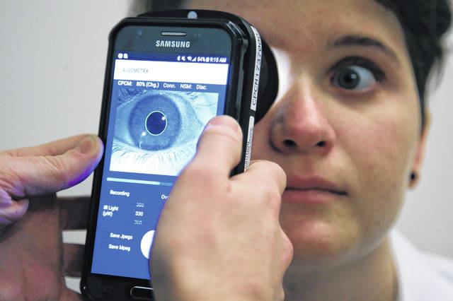 Clinical Research Assistant Kevin Jackson uses AlgometRx Platform Technology on Sarah Taylor's eyes to measure her degree of pain at the Children's National Medical Center in Washington, Monday, Dec. 10, 2018. Children's National Medical Center is testing an experimental device that aims to measure pain according to how pupils react to certain stimuli.