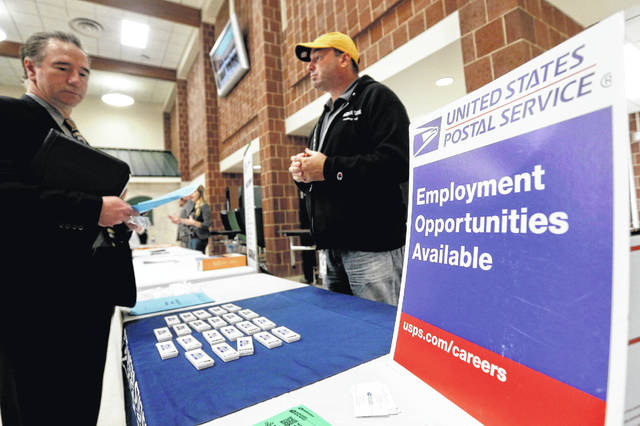 FILE- In this Nov. 2, 2017, file photo a recruiter from the postal service, right, speaks with an attendee of a job fair in the cafeteria of Deer Lakes High School in Cheswick, Pa. Even with fear of a global economic slump depressing stock markets, Friday, Jan. 4, 2019 jobs report for December is expected to offer reassurance that the U.S. economy remains sturdy and on track to expand for a 10th straight year.