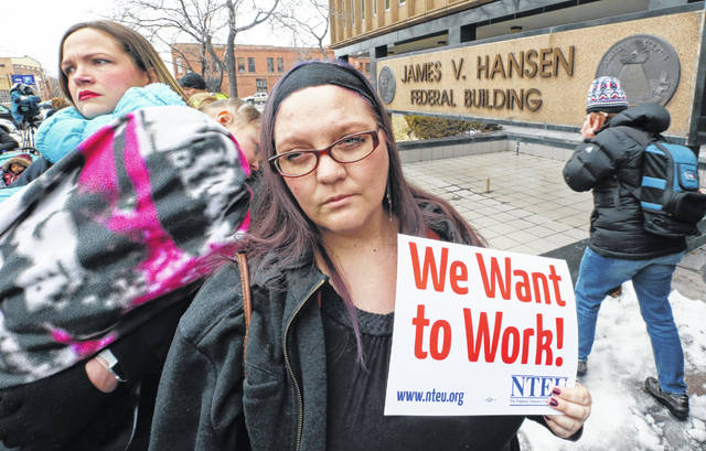 IRS worker Christine Helquist joins a federal workers protest rally outside the Federal Building, Thursday, Jan., 10, 2019, in Ogden, Utah. Payday will come Friday without any checks for about 800,000 federal employees affected by the government shutdown, forcing workers to scale back spending, cancel trips, apply for unemployment benefits and take out loans to stay afloat.