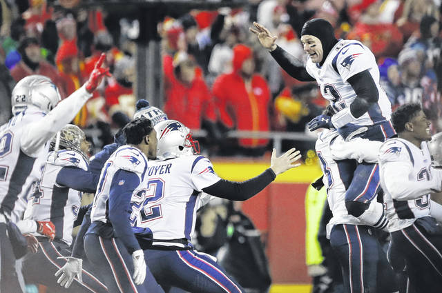 New England Patriots quarterback Tom Brady (12) celebrates with his teammates after the AFC Championship NFL football game, Sunday.