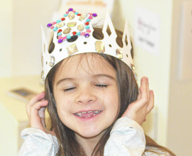 Anya Thomason, 8, of Bluffton tries on the crown she made at an ArtSpace Lima activity Sunday afternoon, prior to the evening performance of Cinderella at Veterans Memorial Civic Center.