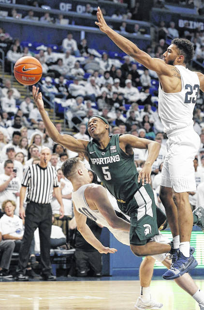 Michigan State's Cassius Winston (5) drives to the hoop as he is fouled by Penn State's Kyle McCloskey (10) during first-half action of an NCAA college basketball game in State College, Pa. on Sunday.