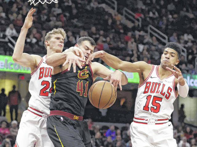 Cleveland Cavaliers' Ante Zizic (41), from Croatia, and Chicago Bulls' Lauri Markkanen (24), from Finland, and Chandler Hutchison (15) battle for the ball in the first half of an NBA basketball game, Monday, Jan. 21, 2019, in Cleveland. (AP Photo/Tony Dejak)