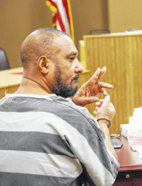 Lima resident Kenneth Cobb, 59, flashed a peace sign to relatives during his appearance Tuesday in Lima Municipal Court.
