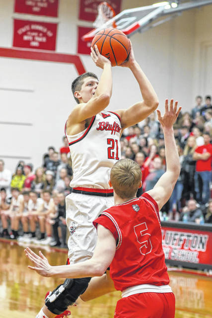 Bluffton's Luke Denecker puts up a shot against Columbus Grove's Gabe Clement during Friday night's Northwest Conference game at Bluffton.