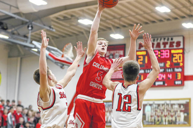 Columbus Grove's Gabe Clement makes a pass against Bluffton's Jared Piercefield (12) and Levi Hohenbrink during Friday night's Northwest Conference game at Bluffton.
