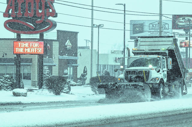 An ODOT snowplow kicks up the snow and slush on Elida Road, Saturday afternoon.