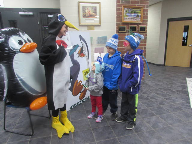 Lindsey Schneeg, volunteer, dressed as a Penguin greets siblings from left Kassidy Badder, 3, Calvin Badder, 7, and Zane Badder, 9, all of Ottawa.
