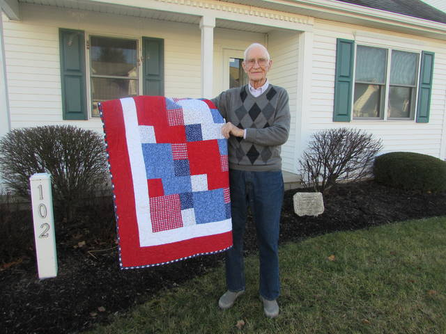 World War II United States Air Force Veteran Robert Bohyer is pictured with a Quilt of Valor he recieved Friday for his service.