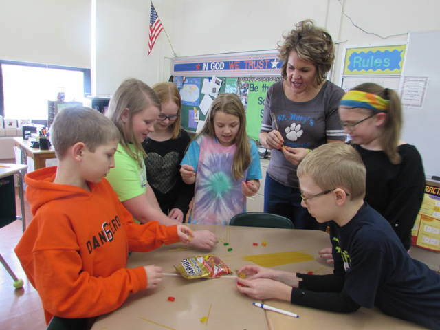 Clockwise from left are St. Mary's school fifth graders constructing a church out of spaghetti noodles and gummy bears, Kylee Schroeder, Sarah Maag, Peyton Schroeder, Kendal Schroeder, Principal Michelle Knippen, and students Kendal Spoors and Carson Schroeder.