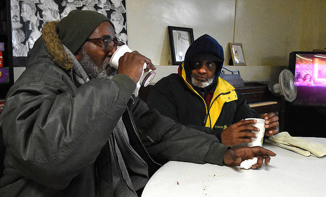 Darryl Thornton, left, of Lima drinks hot coffee in the basement of the YMCA with his friend, Billy Smith. Both came in to get warm from frigid polar vortex on Wednesday morning.