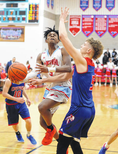 Lima Central Catholic's Biggz Johnson puts up a shot against Crestview's Javin Etzler during Thursday night's game at Msgr. Edward C. Herr Gymnasium.