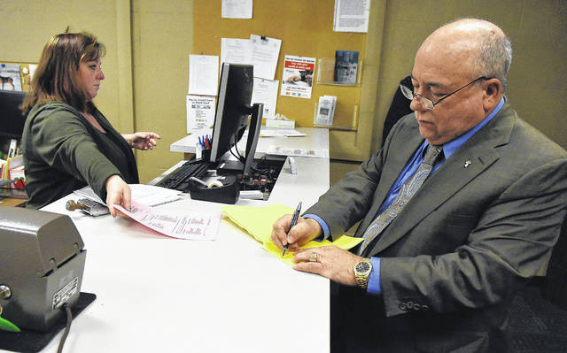 Ray Magnus, right, files a lawsuit against LaMont Monford Sr. on Thursday at the Allen County Clerk of Courts in Lima.