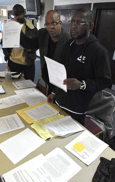 Rev. Ronald Fails, center, of the Lima NAACP, and Leonard Bringham hold documentation containing false statements in the criminal justice center. Craig J. Orosz | The Lima News