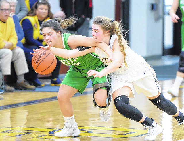 Ottawa-Glandorf's Kelsey Erford, right, fights for a loose ball against Delta's Alayna Mitchell during Saturday's game at Robert J. Hermiller Gymnasium in Ottawa. See more girls high school basketball photos at LimaScores.com.