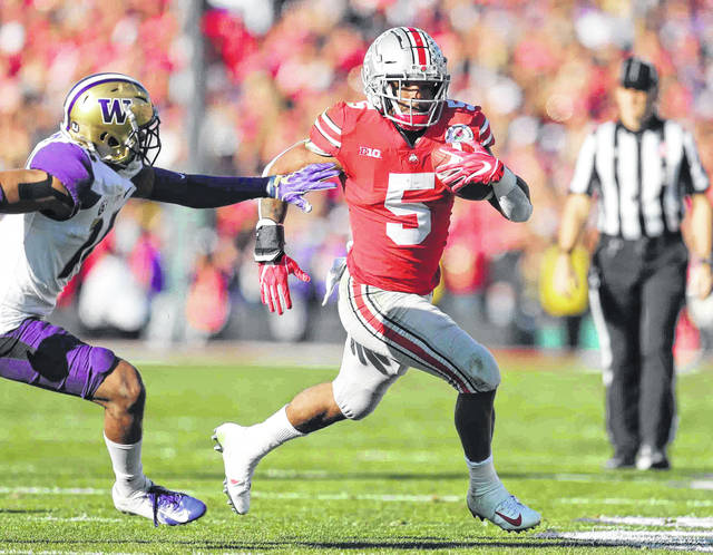 Ohio State's running back Mike Weber Jr. heads upfield as Washington's defensive back JoJo McIntosh tries catch up in the first quarter during the 105th Rose Bowl game Tuesday.