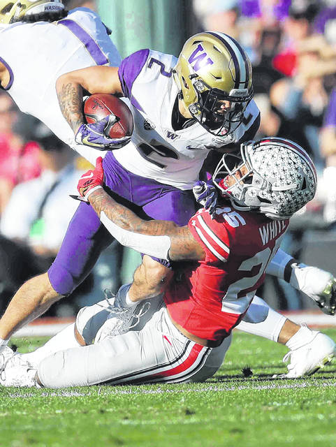 Ohio Stat's safety Brendon White (25) makes the stop on Washington's wide reciever Aaron Fuller during first quarter action during the 105th Rose Bowl game Tuesday.