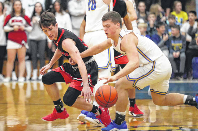 Shawnee's Justin Behnke tries to make the steal against Lucas Metcalfe of Delphos St. John's during Saturday night's game in Delphos.