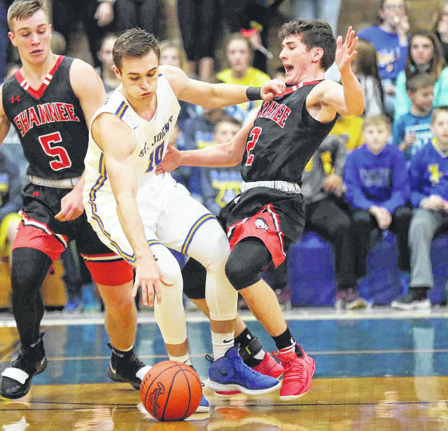 Jared Wurst of Delphos St. John's is called for a charge against Shawnee's Justin Behnke during Saturday night's game in Delphos.