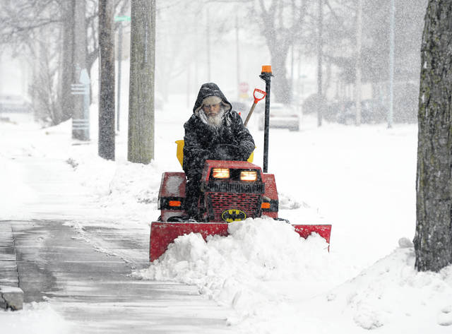 Rob Stidham shovels snow from sidewalks in the midst of a winter storm that was expected to drop five to eight inches of snow throughout the day Saturday.