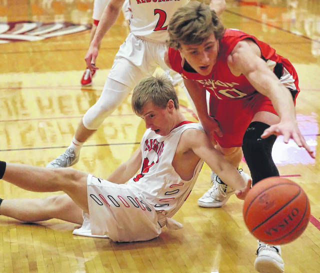 Wapakoneta's Garrett Siefring, left, and Kenton's Jaron Sharp go after a loose ball during Friday night's Western Buckeye League game at Wapakoneta.