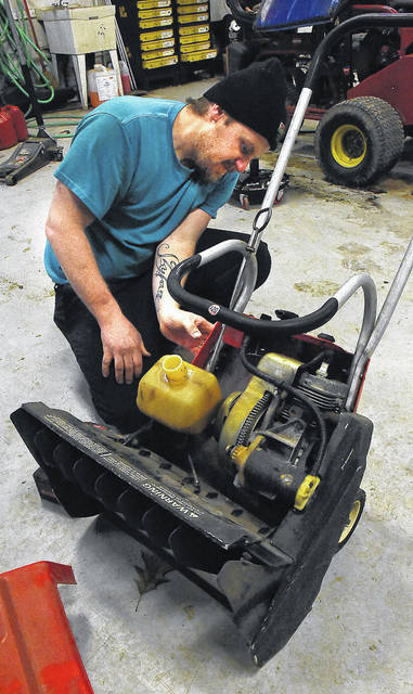 Trevor Stalnaker, a technician at Snappy's Outdoor Equipment in Lima, preps a customer's gasoline snow blower for this winter season.