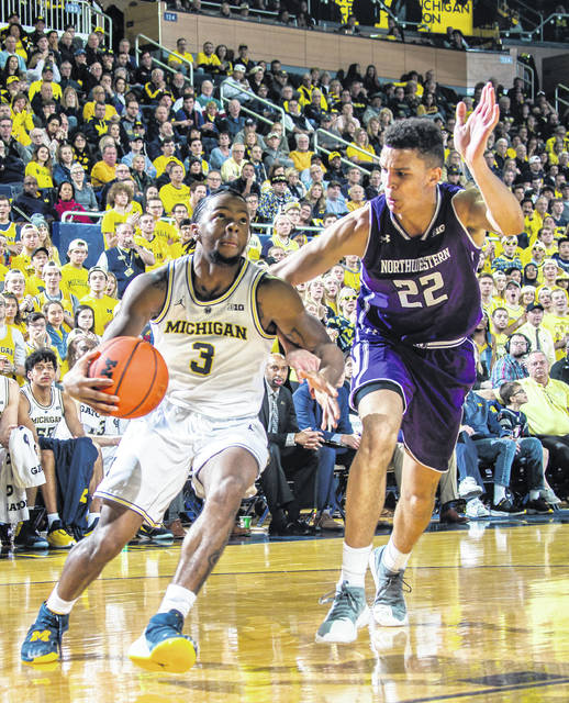 Michigan guard Xavier Simpson (3) drives toward the basket, defended by Northwestern forward Pete Nance (22) during the No. 2 Wolverines' 80-60 win over Northwestern on Sunday night. Michigan is 17-0, the best start in school history.