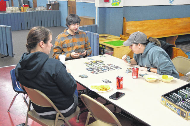 (From left to right) Mary Good, Brian Good and Rosie Hamman enjoy a game of Dominion.