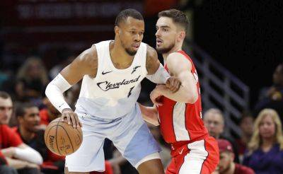 The Cavaliers' Rodney Hood drives against Washington's Tomas Satoransky during Tuesday night's game in Cleveland. (AP photo)