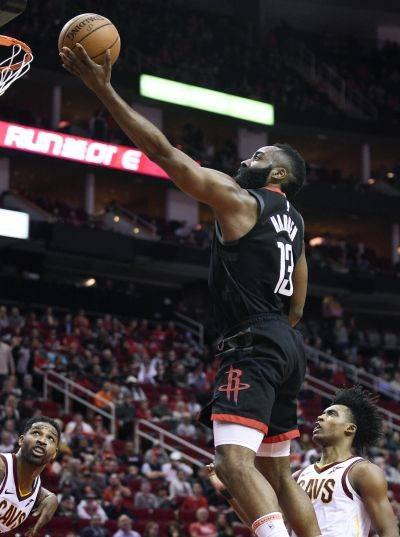 The Rockets' James Harden (13) drives to the basket past Cleveland Cavaliers guard Collin Sexton, right, during Friday night's game in Houston. (AP photo)