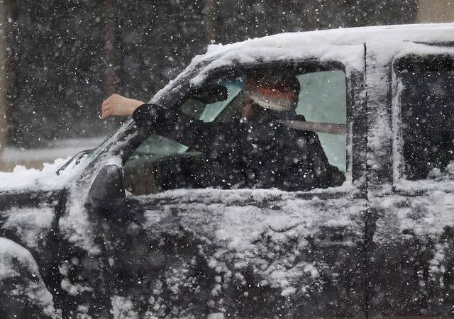 A motorist tries to clear snow from the car's windshield.